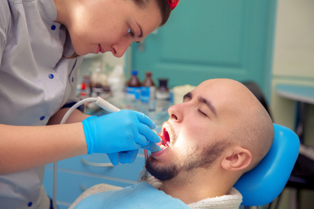 odontolith: handsome guy treats caries teeth in the dental office. Stock Photo