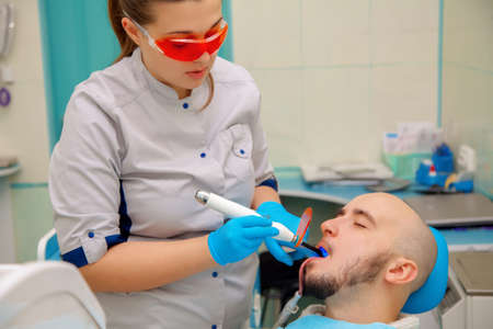 odontolith: handsome male model treats his teeth in a dental office at the doctor.
