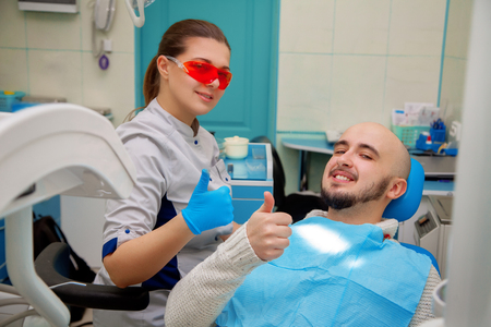 odontolith: Happy doctor and patient in a dental office smiling. Stock Photo
