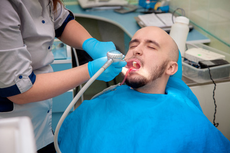 odontolith: photo of male model treats his teeth in dental office.