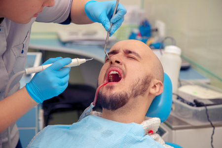 odontolith: man suffering from a toothache at the dentist. Stock Photo