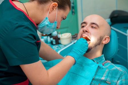 odontolith: man taking care of his health checks teeth at the dentist. Stock Photo