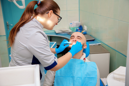 odontolith: Nice adult guy on checking teeth in dental office. Stock Photo