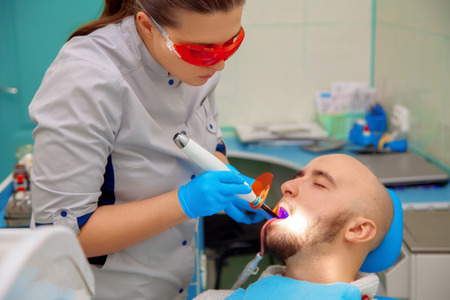 odontolith: nice guy treats caries teeth in the dental office. Stock Photo