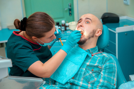 treating: dentist treating teeth to the patient.