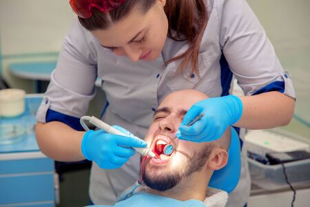 odontolith: photo of handsome guy treats caries teeth in the dental office. Stock Photo