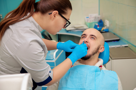 odontolith: Picture of beautiful male model on checking teeth in dental office. Stock Photo