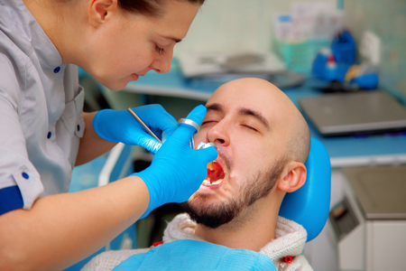 odontolith: Professional dentist treats teeth patient. Stock Photo