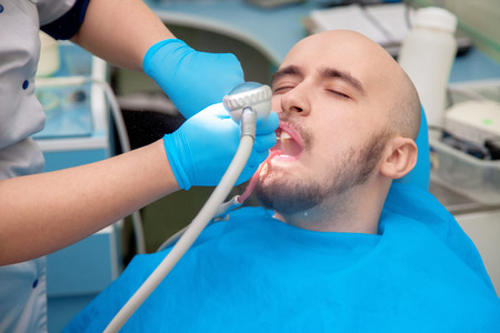 odontolith: Young adult male patient takes a dental attendance in the dentist office. Stock Photo