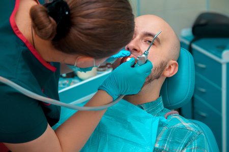 odontolith: Young male checkups his teeth at the dentist doctor. Stock Photo
