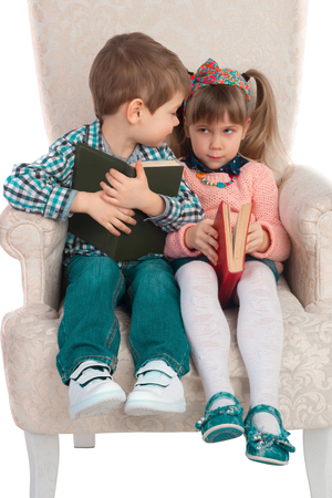 questionably: Little girl suspiciously looks at the boy sitting in a chair