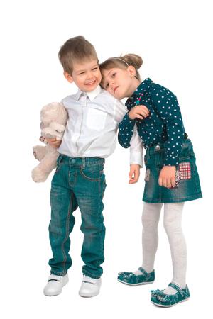 Meisje dat een jonge jongen met een stuk speelgoed op een witte achtergrond koestert Stockfoto