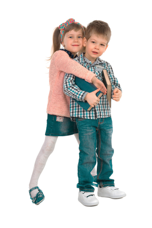 Little girl hugging a boy with books on a white background isolated