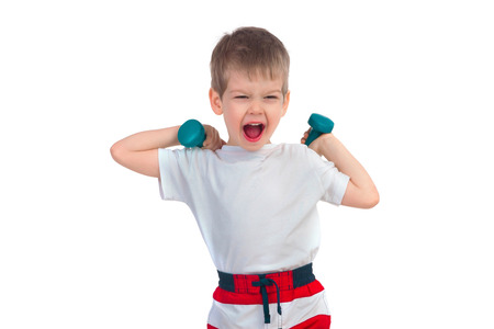 cries: Little boy holding two blue dumbbells and cries on a white background