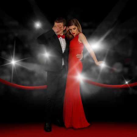 closed club: Elegance young couple on red carpet is hiding from paparazzi flashes