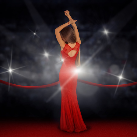 Slim beautiful lady in dress on red carpet is posing in paparazzi flashes