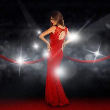 Seksuele jonge dame op de rode loper poseren in paparazzi flitsen Stockfoto