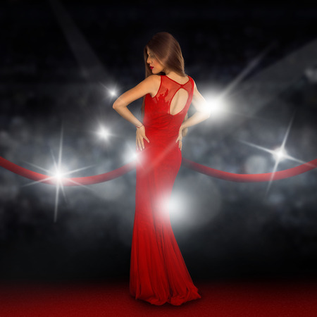 Sexual young lady on red carpet is posing in paparazzi flashes Stock Photo