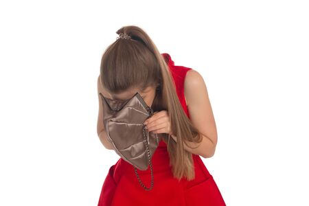 clutch: Girl in a red dress is looking into a clutch