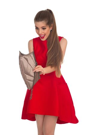 looking into: Girl in a red dress is looking into a clutch