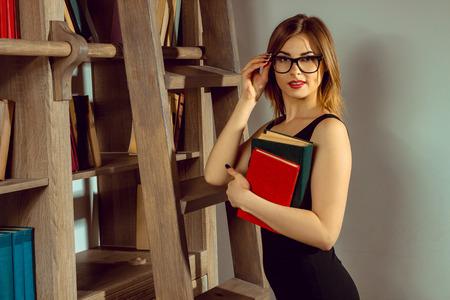 educacion sexual: joven bibliotecario de la mujer en las gafas posando con un libro en la biblioteca junto a la estanter�a y mirando a la c�mara Foto de archivo