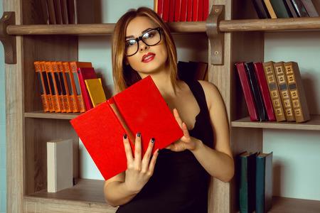bibliothécaire mignon lit un livre avec des lunettes dans la bibliothèque à côté de la bibliothèque