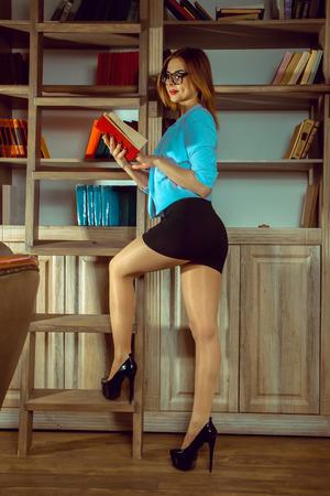 sexy jeune femme bibliothécaire dans les verres lire un livre à côté de la bibliothèque sur des hauts talons