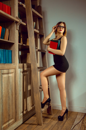 fashionable woman librarian posing with a book in the library next to the bookshelf and looking away Stock Photo