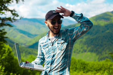 broadly: handsome stylish young man in sunglasses and with a laptop in hands looking aside and smiling broadly in the mountains