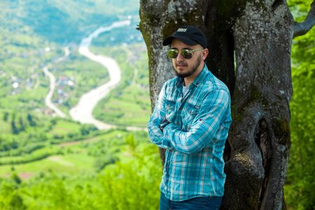 view from behind: Cute young man in sunglasses posing with mountains view from behind with arms crossed