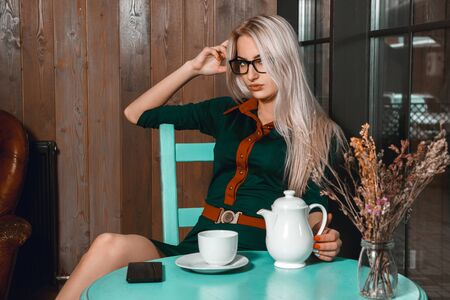 after hours: Attractive young business woman have a coffee break in a cafe. Business concept. Business woman in a cafe. Business after hours. Stock Photo