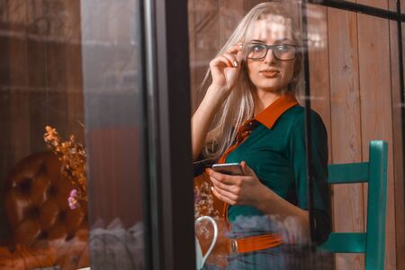 after hours: attractive young businesswoman using her phone and looking at the windows at city cafe. Business concept. Business woman in cafe. Business after hours.