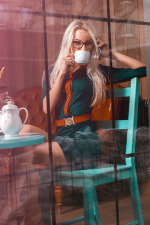 after hours: Beautiful businessowoman drinks coffe in city cafe. Business concept. Business woman in a cafe. Business after hours.