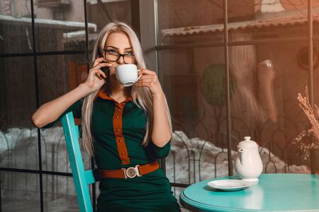 after hours: Business woman at coffee break talking phone and drinks tea. Business concept. Business woman in a cafe. business after hours.