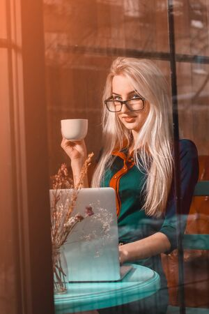 after hours: Gorgeous young happy blond business woman with a cup of tea in a city cafe. Business concept. Business woman works at cafe. Business after hours.