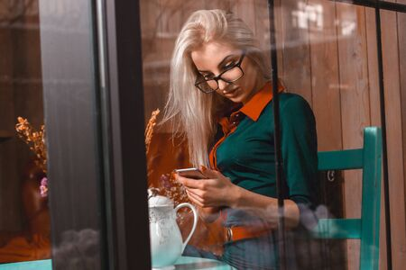 after hours: handsome beautiful woman using a smartphone in a cafe. Business concept. Business woman in a cafe. Business after hours.