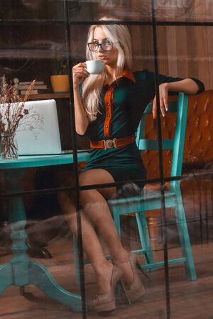 after hours: Hot young blonde business woman drinks coffee in a city cafe. Business concept. Business woman works at cafe. Business after hours.