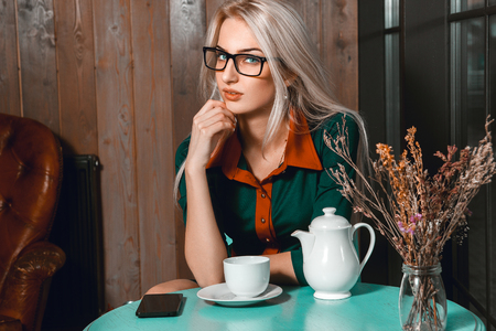 after hours: Pretty young blonde business woman with cup of tea in cafe looking at camera. Business woman in cafe. Business concept. Business after hours.