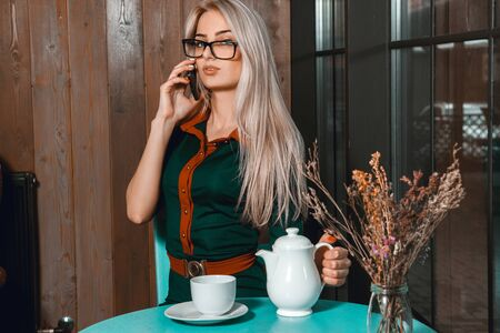 after hours: Serious young blonde business woman talking on the phone in cafe and drinks tea. Business concept. Business woman in cafe. Business after hours. Stock Photo