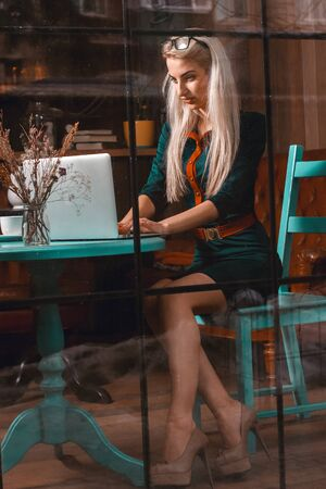 after hours: Serious young blonde woman using laptop in a cafe. Business concept. Business woman works at cafe. Business after hours.