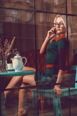 after hours: Sexual Young businesswoman talking on the phone in cafe. Business concept. Business woman in cafe. Business after hours.