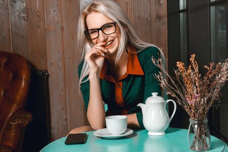 after hours: Smiling beautiful business woman have a coffee break in a cafe. Business concept. Business woman in cafe. Business after hours.
