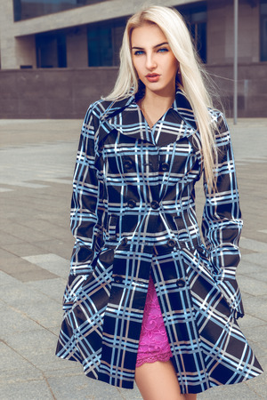 female sexuality: Close up portrait of young blonde fashion model with blue eyes in the coat. fashion model posing outdoors. fashionable and glamour concept. Stock Photo
