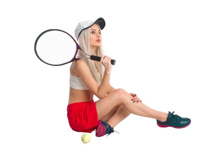 tennis skirt: Beautiful girl sitting in a red skirt with a tennis racket on a white background