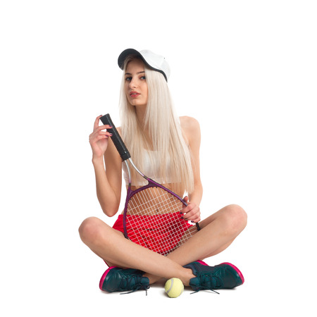 tennis skirt: Beautiful girl sitting in a red skirt with a tennis racket and ball isolated on white background Stock Photo