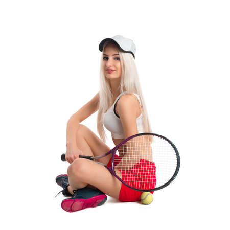 tennis skirt: Beautiful young girl in a baseball cap and a red skirt sitting on isolated white background with a tennis racket and ball Stock Photo