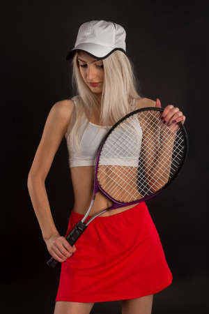 tennis skirt: Beautiful young girl in a red skirt with a tennis racket on a black background