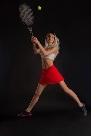 tennis skirt: Beautiful slim girl in a red skirt with a tennis racket on a black background