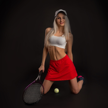 tennis skirt: Beautiful slim girl in a red skirt and a baseball cap on his knees with a tennis racket on a black background