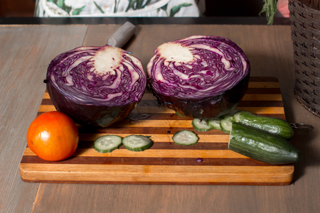 peice: Cut cabbage and sliced cucumber on the board on the kitchen table